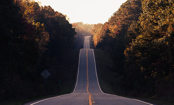 A long road stretches off into the distance, climbing over hills and cutting through a forest.